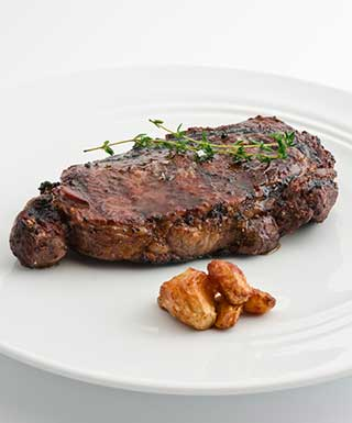 ribeye steak and vege on white plate with white background